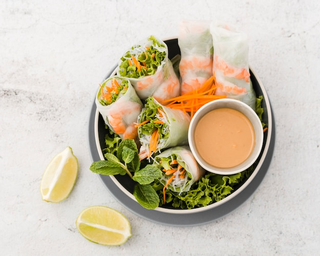 Top view of bowl of shrimp rolls with sauce and lemon Free Photo