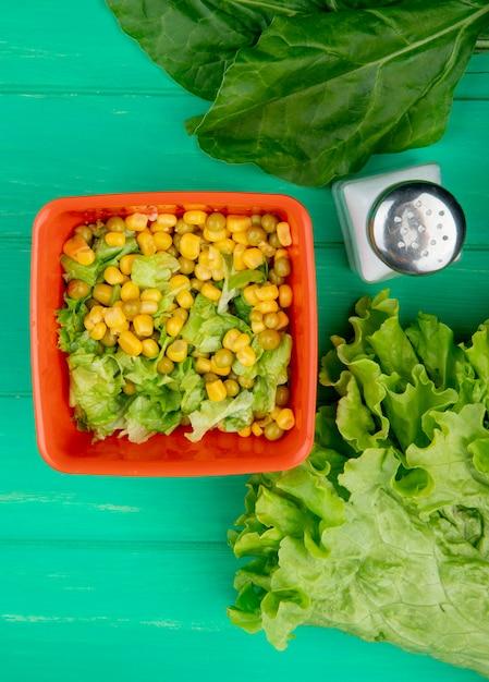 Vista superiore della ciotola di pisello giallo con lattuga e lattuga affettate sale integrale su verde Foto Gratuite