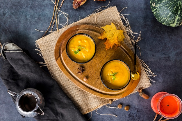 Top view of bowls of squash soup on wooden board Free Photo
