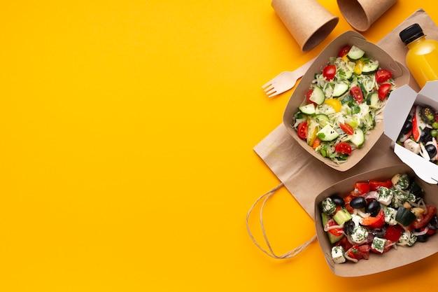 黄色の背景にサラダトップビューボックス Premium写真