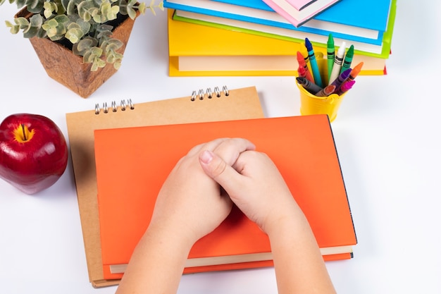 Top view boy join hand together on stack of books on white background / back to school Premium Photo