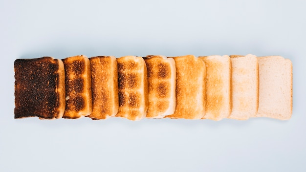 Top view of bread slices at varying stages of toasting arranged in row on white background Free Photo