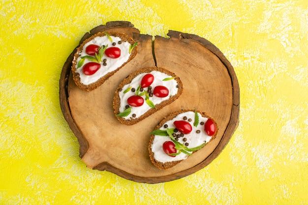 Vista dall'alto di toast di pane con panna acida e cornioli sulla superficie gialla Foto Gratuite