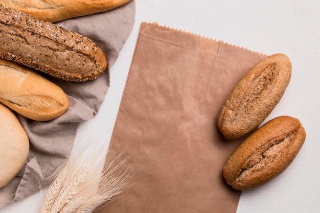 Вид сверху хлеба и бумажной упаковки с пшеницей Бесплатные Фотографии