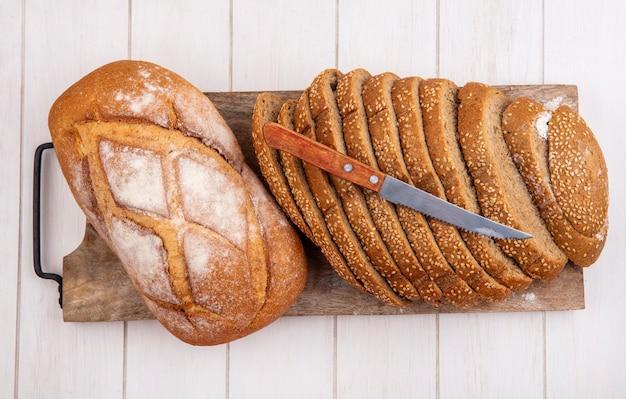 Vista dall'alto di pane come pannocchia con semi marrone a fette e pane croccante con coltello sul tagliere su sfondo di legno Foto Gratuite