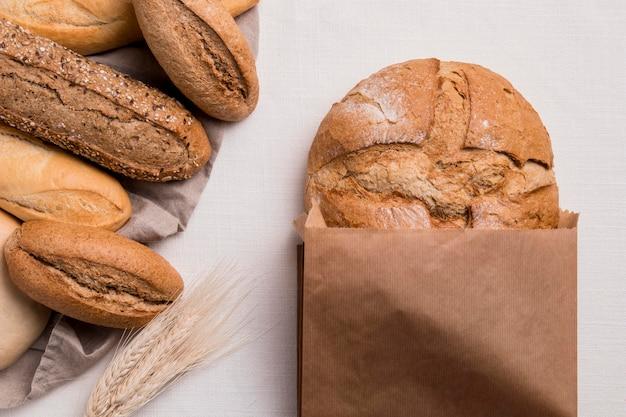 Вид сверху на хлеб, смешанный с бумажной упаковкой и пшеницей Бесплатные Фотографии