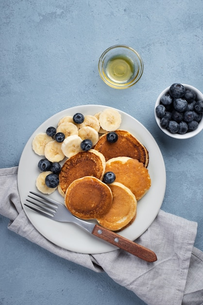 Top view of breakfast pancakes on plate with blueberries and banana slices Free Photo