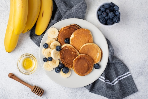 Top view of breakfast pancakes on plate with honey and bananas Free Photo