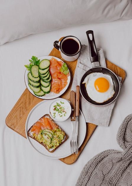 Vista dall'alto di panini per la colazione sul letto con pane tostato e uovo fritto Foto Gratuite