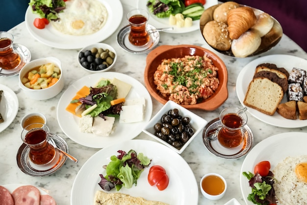 Top view breakfast set scrambled eggs with tomatoes a variety of cheeses vegetables olives honey with tea and bread on the table Free Photo