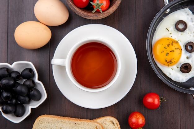 Vista dall'alto del set colazione con tazza di tè sul piattino uovo fritto olive nere fette di pane uova e pomodori su legno Foto Gratuite