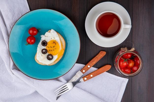 Vista dall'alto del set colazione con uovo fritto oliva e pomodori nel piatto con forchetta e coltello su stoffa e ciotola di pomodoro con tazza di tè su legno Foto Gratuite