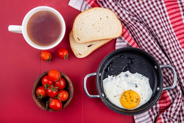 Vista dall'alto del set colazione con padella di uovo fritto e ciotola di fette di pane al pomodoro su panno plaid e tazza di tè sul rosso Foto Gratuite