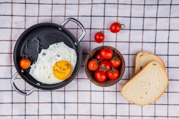 Vista dall'alto del set da colazione con padella di uovo fritto e ciotola di pomodoro con fette di pane su un panno a quadri Foto Gratuite