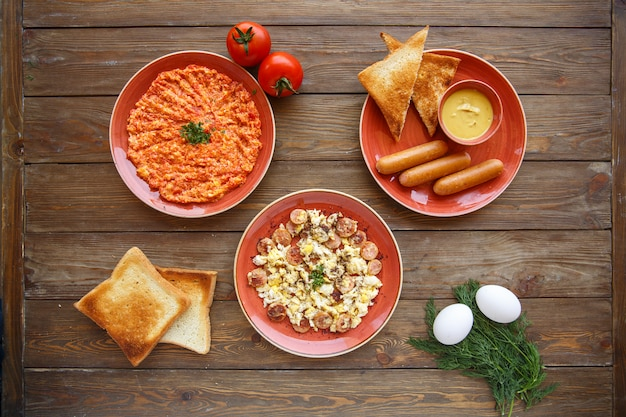 Top view of breakfast setup with egg and tomato dish and sausages dishes Free Photo