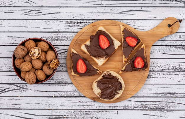 Top view of breakfast toasts with chocolate and strawberry on cutting board and walnuts in bowl on white wooden surface horizontal Free Photo