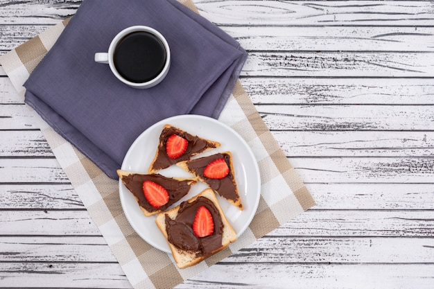 Top view of breakfast toasts with chocolate and strawberry on plate and coffee on white wooden surface horizontal Free Photo