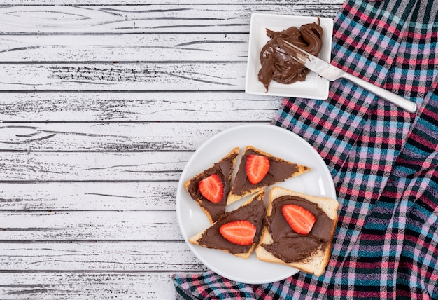 Top view of breakfast toasts with chocolate and strawberry with copy space on white wooden background horizontal Free Photo