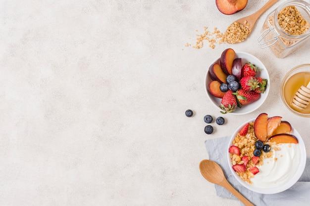 Вид сверху завтрак с фруктами и йогуртом на столе Premium Фотографии