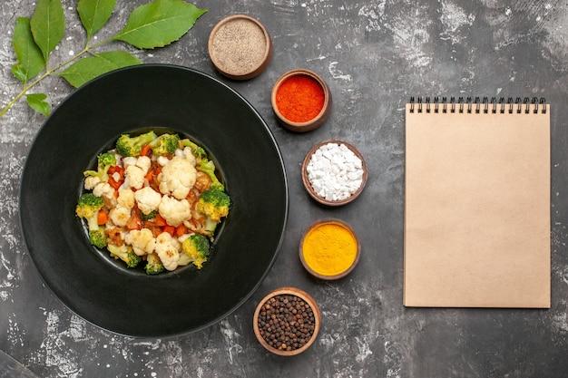 Vista dall'alto insalata di broccoli e cavolfiori sul piatto ovale nero spezie diverse in piccole ciotole un taccuino sulla superficie scura Foto Gratuite