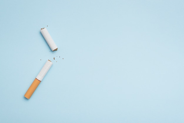 Top view of broken cigarette on blue background Free Photo