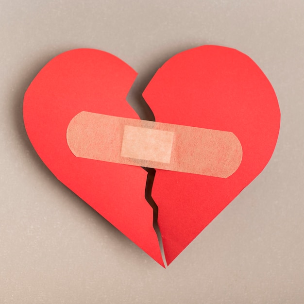 Top view broken heart with band-aid Premium Photo