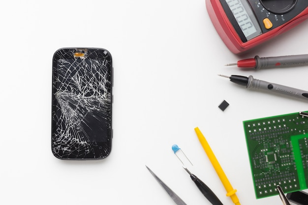 Top view broken phone with electronic tools Free Photo