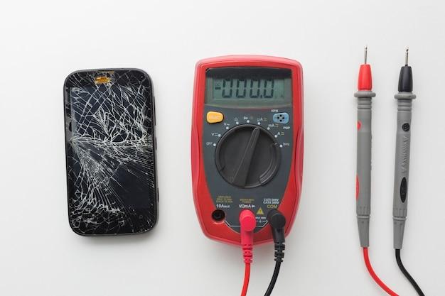 Вид сверху сломанный смартфон с мультиметром Premium Фотографии