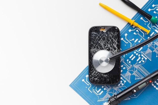 Вид сверху сломанный смартфон с инструментами для ремонта Premium Фотографии