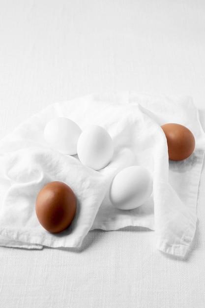 Вид сверху коричневые и белые яйца с кухонным полотенцем Бесплатные Фотографии