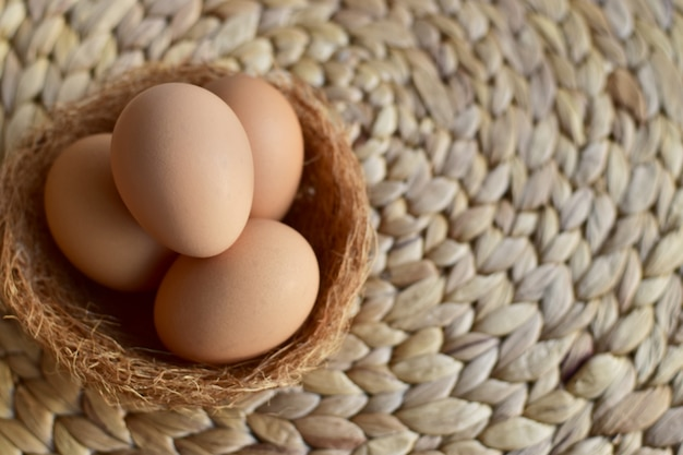 Top view of brown chicken/hen eggs in a nest on top of a natural mat Premium Photo