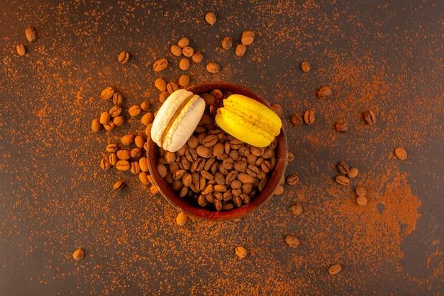 Una vista dall'alto semi di caffè marrone all'interno del piatto marrone con macarons francesi sul tavolo marrone Foto Gratuite