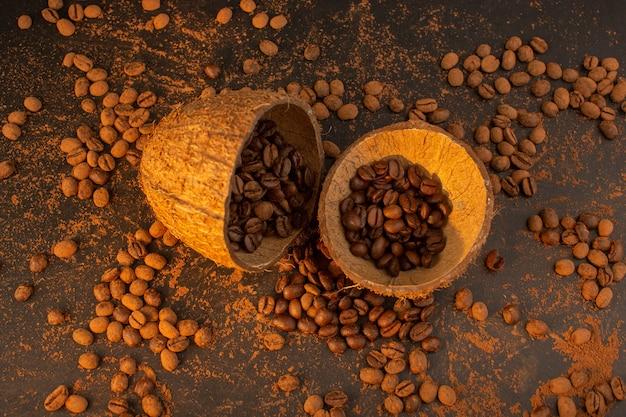 Una vista dall'alto semi di caffè marrone all'interno e all'esterno di gusci di noce di cocco sul granulo marrone del chicco del seme di caffè dello scrittorio Foto Gratuite