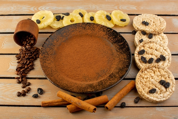 A top view brown powdered coffee inside black plate with dried pineapple cinnamon and crackers on the cream rustic table coffee seed drink photo grain Free Photo