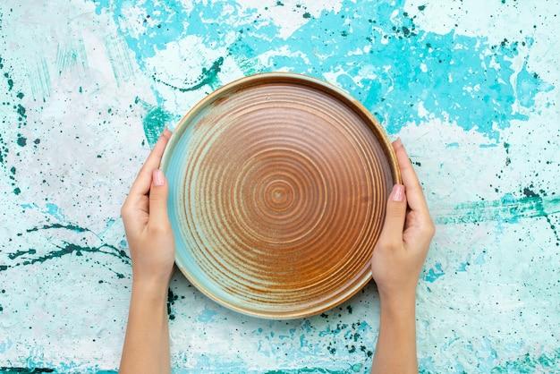 Vista dall'alto dello stampo rotondo marrone tenuto dalla femmina su un pasto di cibo torta azzurro Foto Gratuite