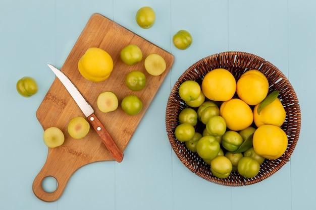 Vista dall'alto di un secchio di pesche gialle con fette di prugne ciliegia verde su una tavola di cucina in legno con coltello su sfondo blu Foto Gratuite