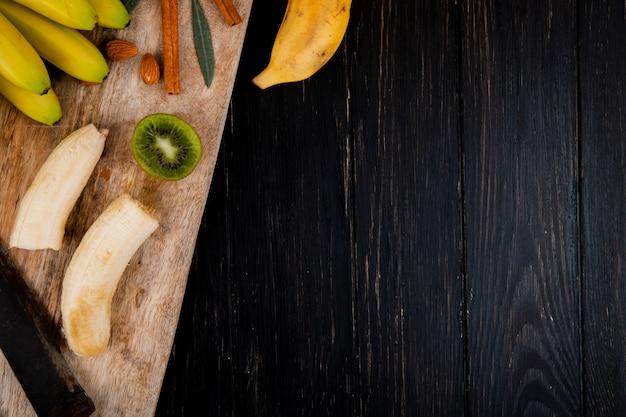 Vista superiore di un mazzo di banana con mandorle, bastoncini di cannella e vecchio coltello da cucina su un tagliere di legno sul nero con lo spazio della copia Foto Gratuite