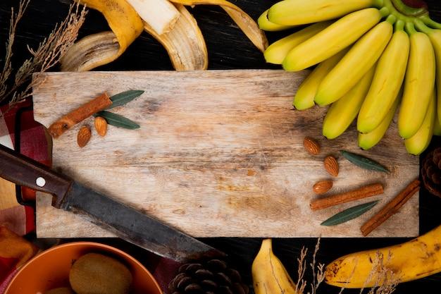 Vista superiore di un mazzo di banana con mandorle, bastoncini di cannella e vecchio coltello da cucina su un tagliere di legno sul nero Foto Gratuite