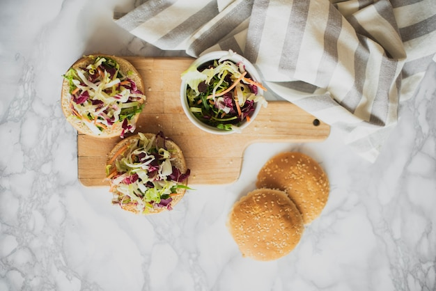 Top view buns with fresh salad on table Free Photo