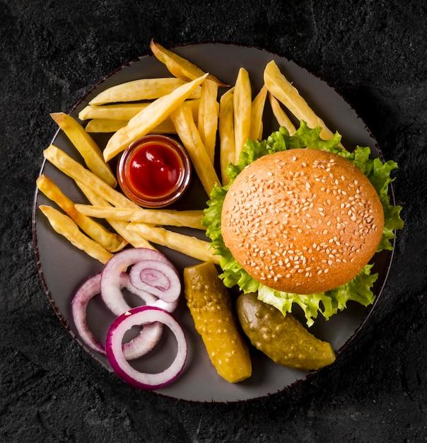 Гамбургер и картофель на тарелке с солеными огурцами, вид сверху Бесплатные Фотографии