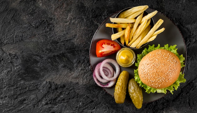 Top view burger and fries on plate with pickles and copy-space Free Photo