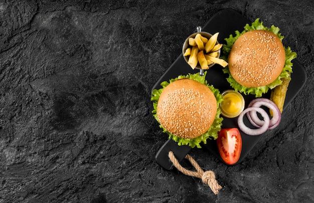 Вид сверху гамбургеры и картофель на разделочной доске с солеными огурцами и копией пространства Бесплатные Фотографии