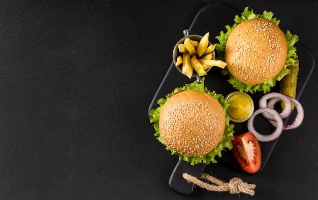 ピクルスとコピースペースのあるトップビューのハンバーガーとフライドポテト 無料写真