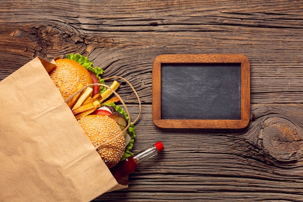 Top view burgers in a bag with chalkboard Free Photo