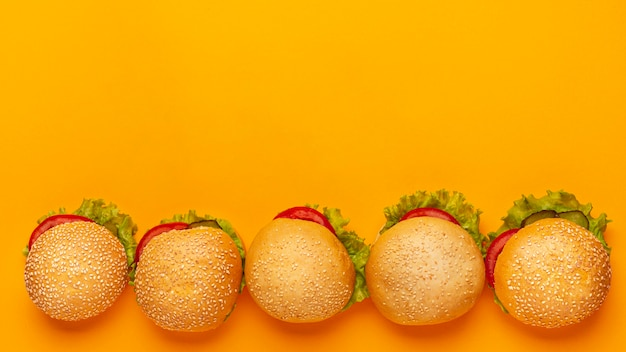 Top view burgers frame with orange background Free Photo