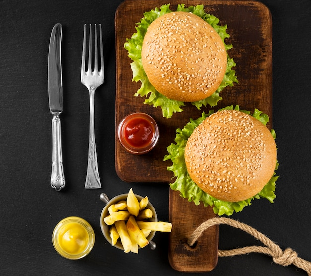 Top view burgers and fries on cutting board Free Photo