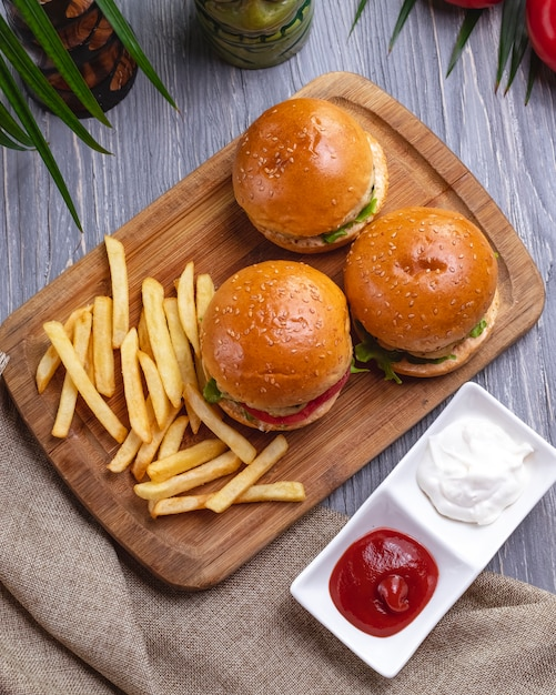Top view burgers with french fries ketchup with mayonnaise and tomatoes Free Photo