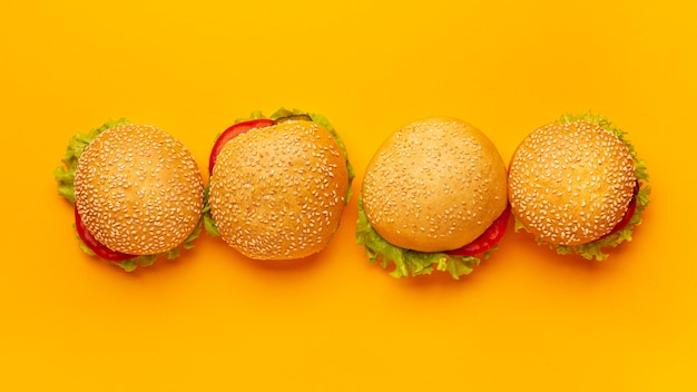 Top view burgers with orange background Free Photo