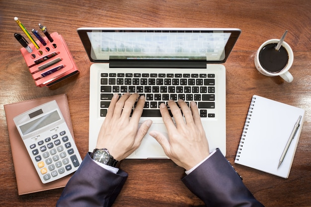 Top view of business man hands working on laptop or tablet pc on wooden desk. Free Photo
