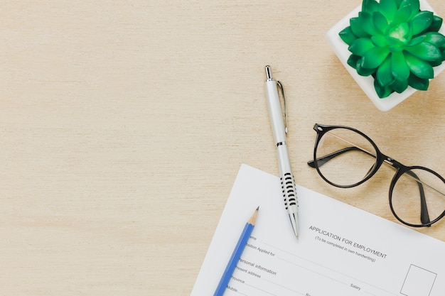 Top view business office desk background.the applying for a job form and pen pencil eyeglasses tree on wooden table background with copy space. Free Photo
